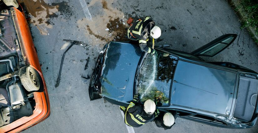 Aerial view of car accident with firefighters